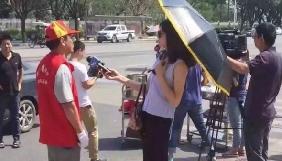 У Китаї журналістку відсторонили від роботи через окуляри і парасольку